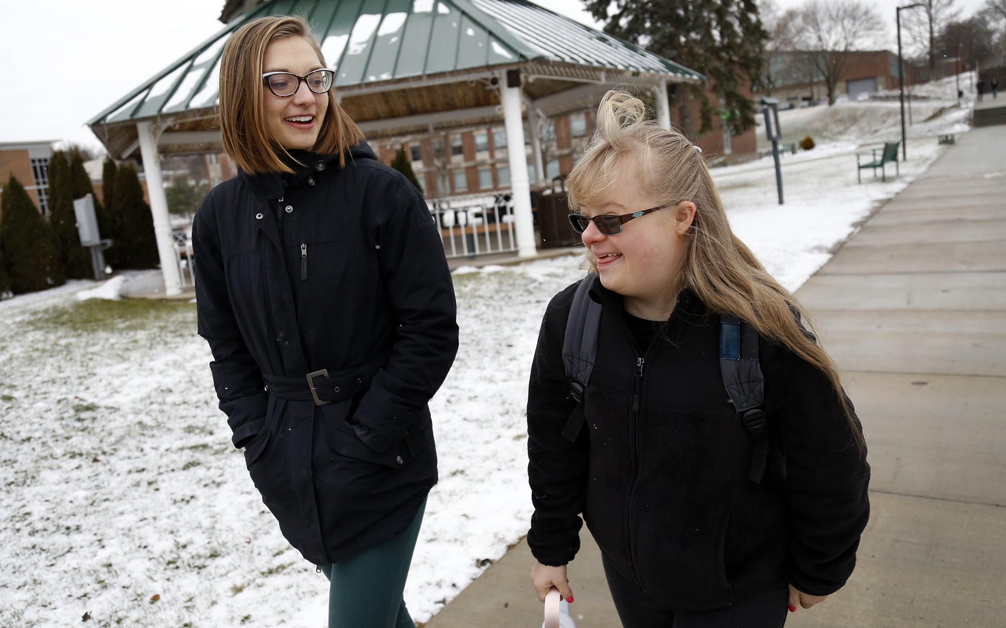 Emilia Hobbs, assistant coordinator for Slippery Rock University's Rock Life program, (left) talks with Nicolette Fenello, a 21-year-old second-year student at the university, as they walk across campus on Jan. 25, 2018. (Photo by Ryan Loew/PublicSource)